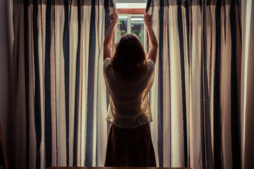 Young woman opening the curtains at sunrise