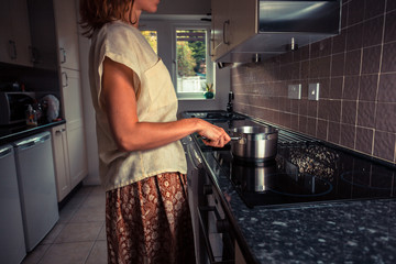 Young woman in kitchen cooking with saucepan