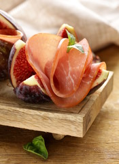 ripe purple figs with smoked ham - a traditional appetizer