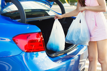 Woman putting shopping bags inside trunk of her blue car