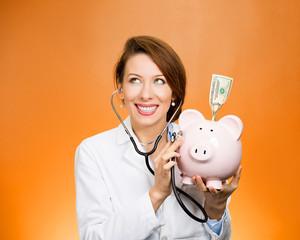 Doctor, nurse listening with stethoscope to piggy bank