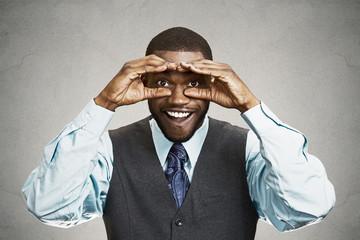 Curious man looking surprised shocked through binoculars