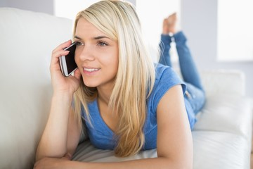 Relaxed beautiful woman using mobile phone in living room