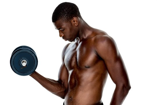 Serious fit shirtless young man lifting dumbbell