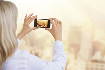 Woman taking photo of city with mobile phone