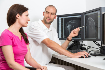 Radiologist councelling a patient using MRI images