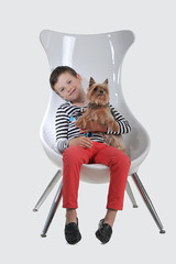 a little boy 7 years old sitting on a chair with a small dog - Y