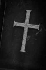 stone cross on black marble