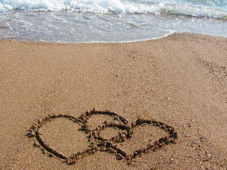 Two hearts drawn on the beach.