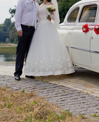 Bride and groom posing by a car