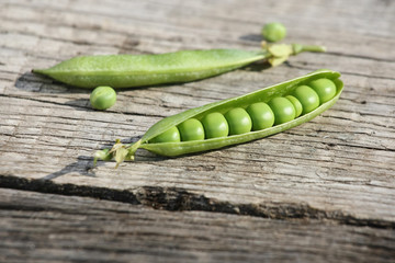 fresh pea pods onwooden boards