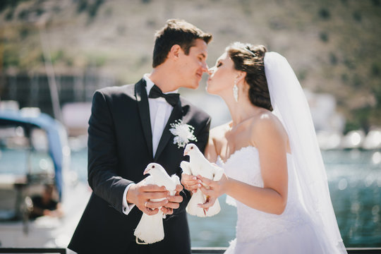 Bride and groom posing with white wedding doves