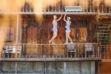 Funny couple in retro swimsuit near hose
