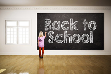 young girl writing 'back to school' at a blackboard