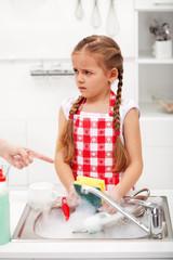 Sulking little girl doing the dishes