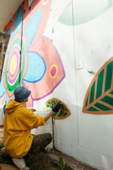 Image of guy drawing graffiti on wall