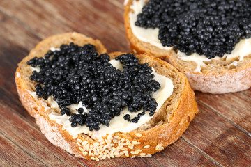 Slices of bread with butter and black caviar