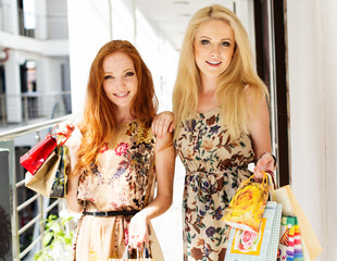 Two attractive happy girls out shopping