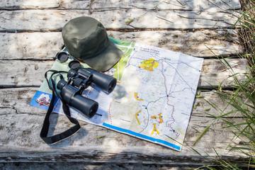 Adventurous supplies. Hat, binoculars and map.