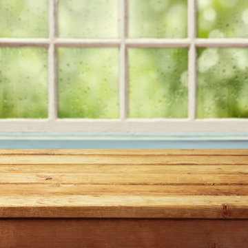 Empty wooden deck table and window with rain drops