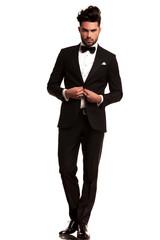 elegant man in tuxedo unbuttoning his coat