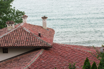 roofs of red tiles on a background of the sea