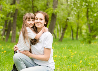 Mother and daughter embrace in the park