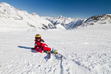 Girl skier sitting on a ski slope