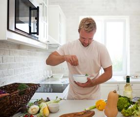 Handsome man cooking at home preparing salad in kitchen