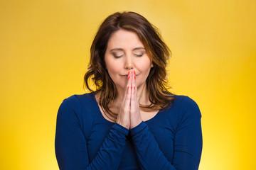 Headshot woman praying isolated on yellow background
