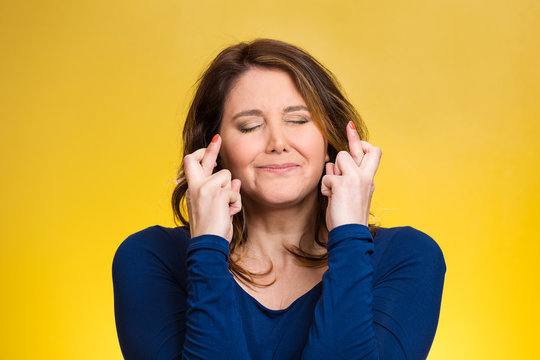 Woman, mother crossing her fingers on yellow background