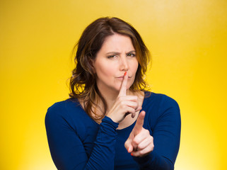 Woman placing finger, hand on lips, shhh gesture, be quiet