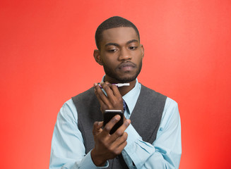 Man shaving reading news on smartphone, red background