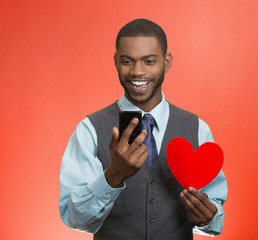 Happy man looking at smart phone, holding red heart in hand