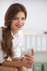 Businesswoman sending message with smartphone sitting in the of