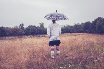 Young woman with umbrella standing in field