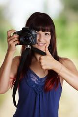 junge Frau mit Kamera und Daumen hoch