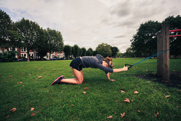Woman working out with resistance band in the park