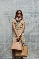 Woman posing with bags and sunglasses outdoors