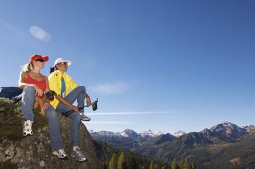 Zwei Frauen, im Bergen auf Felsen sitzen