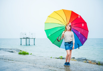 Outdoor portrait of a cute little girl with colorful umbrella