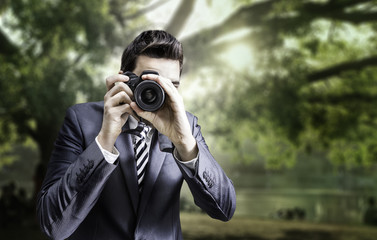 Male photographer focusing and composing an image in the park