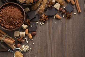 Foto op Plexiglas Chocolade chocolate, cocoa, nuts and spices on wooden background, top view