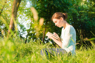 girl sitting in park and writing