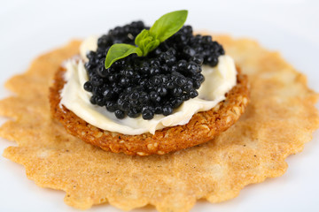 Black caviar with crispy bread on plate closeup