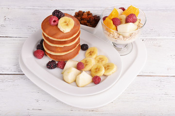Pancake with fruits and muesli on plate on table close up