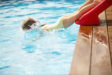Junges Mädchen rutscht ins Schwimmbad