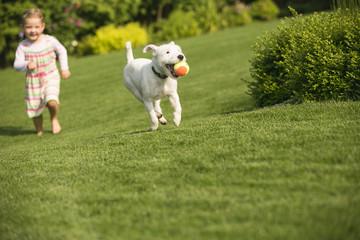 Junges Mädchen spielt mit Hund im Garten