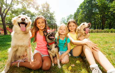 Three girls with dogs sitting on grass outside