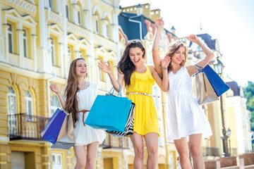 Best friends do shopping. Girls holding shopping bags and walk a
